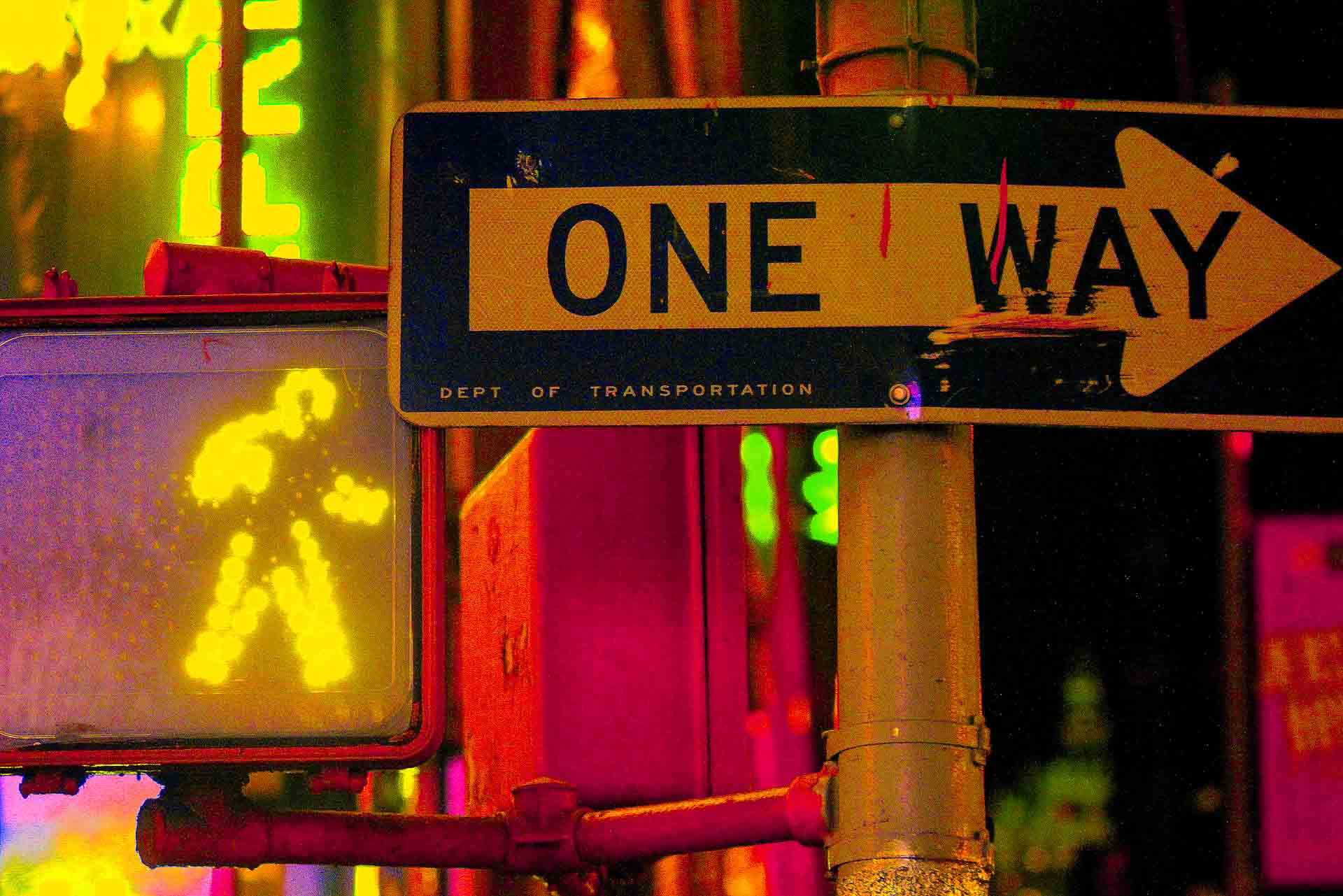 a walk sign and One Way sign in New York City