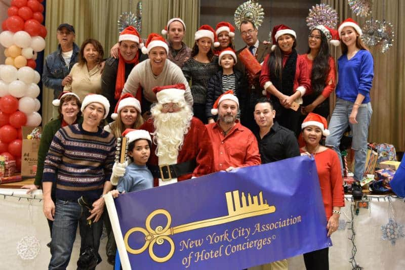 Members of the New York City Association of Hotel Concierges celebrate a charity Christmas in the South Bronx